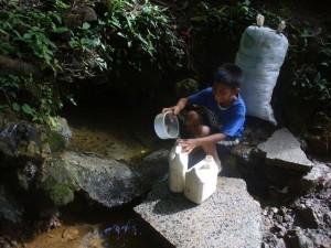 Ein Junge füllt an der Quelle einige Behälter, die er dann später nach Hause trägt.